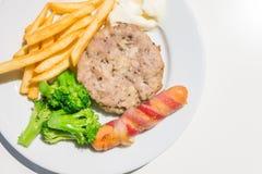 Le bifteck, la saucisse et le lard hachés de porc roulent avec des pommes frites Photo libre de droits