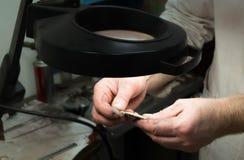 Le bijoutier examine le produit Photo stock