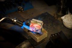 Le bijoutier fond avec de l'argent ou l'or de flamme sur le vieil établi photos stock