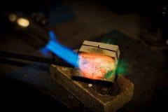 Le bijoutier fond avec de l'argent ou l'or de flamme sur le vieil établi photographie stock