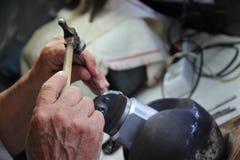 Le bijoutier monnaye la décoration argentée dans l'atelier Photographie stock