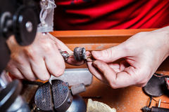 Le bijoutier polit la boucle d'oreille d'or Images stock