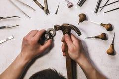 Le bijoutier réduit la taille de l'anneau d'or dans l'atelier photos stock