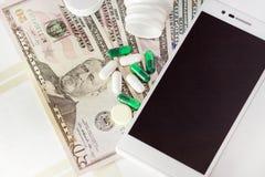Le billet de banque avec l'argent du dollar, téléphone portable, comprimés, a mis des médecines en bouteille sur des bonnots, pla Photos libres de droits