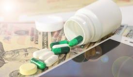Le billet de banque avec l'argent du dollar, téléphone portable, comprimés, a mis des médecines en bouteille sur des bonnots, pla Photographie stock