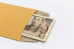 Le billet de banque japonais 10.000 Yens dans l'enveloppe brune pour donnent et réussite commerciale et achats Photographie stock