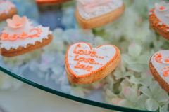 Le biscuit avec amour de lettrage de lustre se trouve sur la table en verre Photos stock