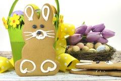 Le biscuit heureux de lapin de pain d'épice de thème de jaune de Pâques et de vert de chaux avec le panier, les tulipes, et les o Photographie stock libre de droits