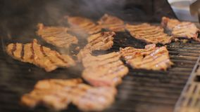 Le bistecche della carne sono cucinate su una griglia del gas Piatti saporiti della carne all'aperto Il fumo viene da alimento Il video d archivio