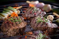 Le bistecche di manzo deliziose con la verdura su un barbecue grigliano Fotografia Stock Libera da Diritti