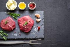 Le bistecche di manzo della carne cruda sull'ardesia nera imbarcano, spezie ed ingrediente Fotografia Stock
