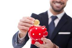 Le bitcoin de la baisse une d'homme d'affaires dans le rouge a pointillé le plan rapproché de tirelire Photos libres de droits