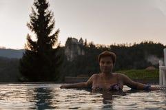 Le blanc a bronzé la femme dans la piscine extérieure au coucher du soleil Photo libre de droits