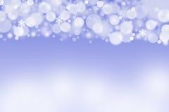 Le blanc a brouillé des boules et des flocons de neige sur un fond bleu Photos stock