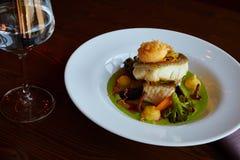 Le blanc a cuit des poissons de sandre en sauce verte à pesto avec des légumes pour cuire le brocoli à la vapeur, carottes, bette Photographie stock