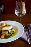 Le blanc a cuit des poissons de sandre en sauce verte à pesto avec des légumes pour cuire le brocoli à la vapeur, carottes, bette Images libres de droits