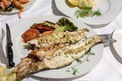 Le blanc délicieux a grillé des poissons avec garnissent des légumes Images stock