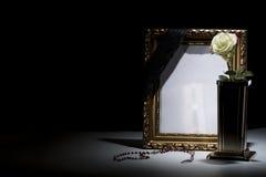 Le blanc a doré le cadre de deuil avec le vase en bronze, rose de blanc, chapelet Images libres de droits