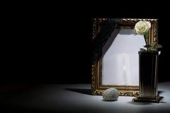 Le blanc a doré le cadre de deuil avec le vase en bronze, rose de blanc, pierre, Photographie stock libre de droits