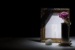 Le blanc a doré le cadre de deuil avec le vase en bronze, rose de rose, pierre Image stock