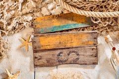 Le blanc en bois de planche signent plus de le sable et le filet de pêche Photos stock