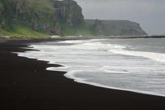 Le blanc ondule sur la plage noire Image libre de droits