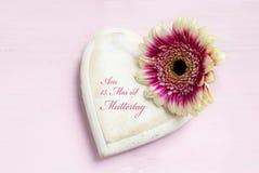 Le blanc a peint la forme en bois de coeur et une tête de fleur sur un p lumineux Image stock