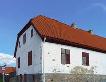 Le blanc a peint la vieille maison avec le toit rouge dans Ventspils Photographie stock