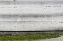 Le blanc a peint le mur en bois avec l'herbe verte comme fond Photos stock