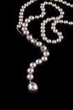 Le blanc perle le collier sur le noir Image stock