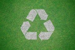 Le blanc réutilisent le logo peint sur le champ d'herbe verte de la vue supérieure r photographie stock