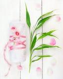 Le blanc a roulé vers le haut de la serviette avec les fleurs et les pousses de bambou roses Photo stock