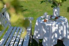 Le blanc a servi la table avec du café, des caneles et des fleurs photos stock