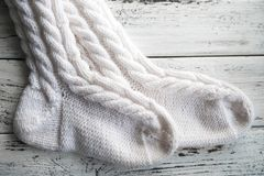 Le blanc a tricoté les chaussettes, chaussettes faites main sur le fond blanc Texture des choses tricotées images stock