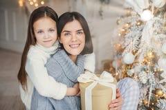 Le bleu adorable a observé le petit enfant que les huggs avec grand aiment sa mère qui tient le boîte-cadeau enveloppé, arbre prè photographie stock