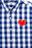 Le bleu a boutonné la chemise à carreaux avec le coeur, l'amour ou le speci de feutre de rouge Photographie stock