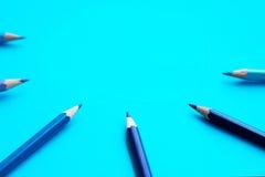 Le bleu a coloré des crayons dans un demi-cercle - fond bleu Photographie stock libre de droits