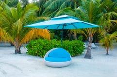Le bleu détendent le lit de chaise du SOLEIL sur le sable couvert de parapluie - station de vacances Images libres de droits