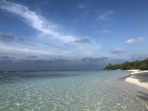 Le bleu de ciel clair comme de l'eau de roche blanc arénacé des Maldives de plage ombrage les vagues vertes de récif de lagune photo libre de droits