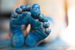 Le bleu de petit enfant peint pieds Photo stock