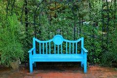 Le bleu de turquoise vif a coloré le banc en bois sur la voie de brique de terre cuite dans le jardin vert images stock