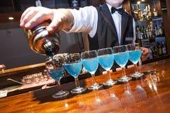 Le bleu de versement de barman coloré boit aux verres sur la barre Co Images libres de droits