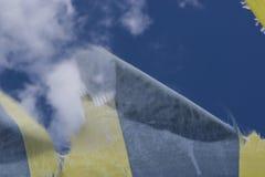 Le bleu et le jaune ont réduit en lambeaux le tissu flottant dans le vent sur le fond de ciel Image stock
