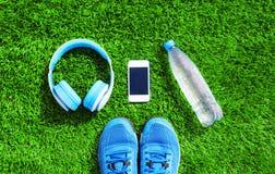 Le bleu les écouteurs et le smartphone blanc avec des chaussures d'espadrilles de sports, bouteille de l'eau sur une herbe verte  Image stock