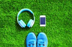Le bleu les écouteurs et le smartphone blanc avec des espadrilles de sports chausse sur un fond texturisé d'herbe verte, vue supé Photo stock