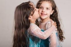 Le bleu matcing de port adorable de grande et petite soeur habille la pose ensemble heureusement, fond de studio Photo libre de droits