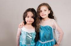 Le bleu matcing de port adorable de grande et petite soeur habille la pose ensemble heureusement, fond de studio Photos libres de droits