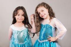 Le bleu matcing de port adorable de grande et petite soeur habille la pose ensemble heureusement, fond de studio Images libres de droits