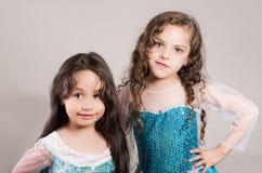 Le bleu matcing de port adorable de grande et petite soeur habille la pose ensemble heureusement, fond de studio Images stock