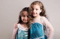 Le bleu matcing de port adorable de grande et petite soeur habille la pose ensemble heureusement, fond de studio Photos stock